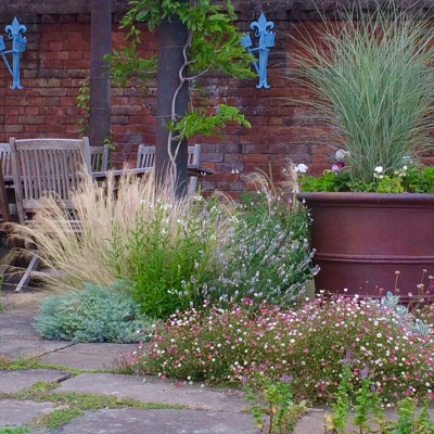 A contrast of frothy, airy planting and strong lines of wood, stone and copper.