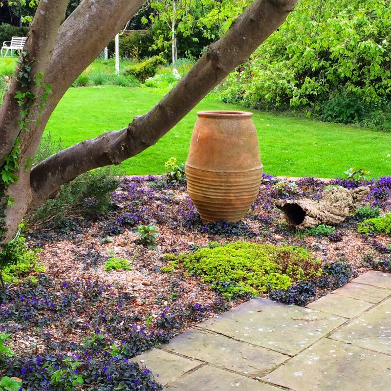 A contemporary urn under a traditional cobnut tree