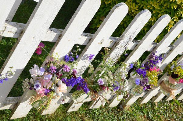Jam jar flowers on a picket fence.