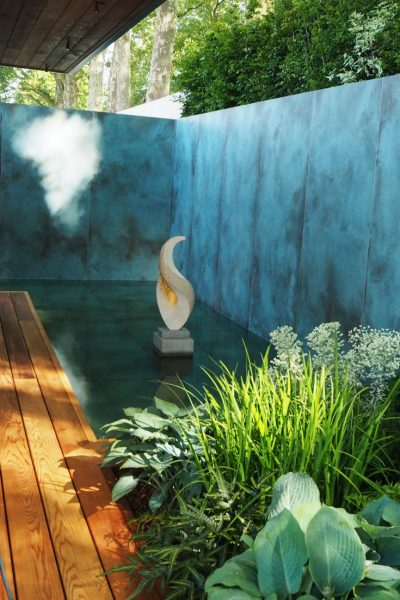 A garden pond going right up to the wall of an urban garden #backyard #gardendesign