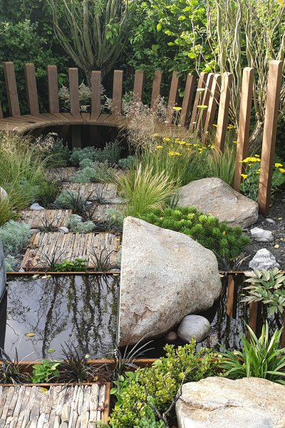 Curved pond and garden bench at RHS Hampton Court Garden Festival