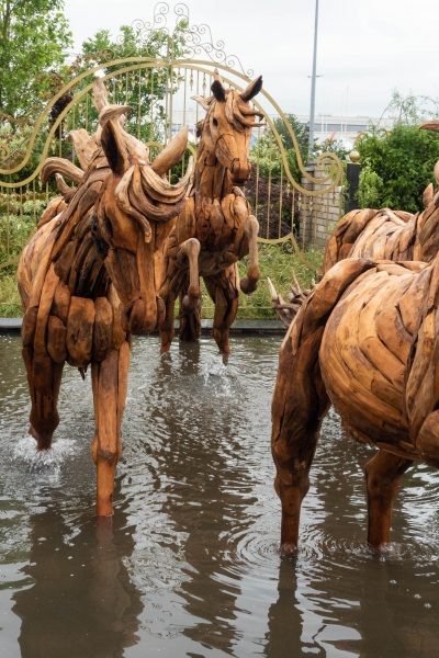 Horse statues galloping through a pond in the Revelation Garden.