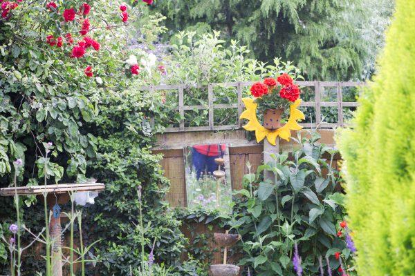 Bird feeders and garden art in a small garden